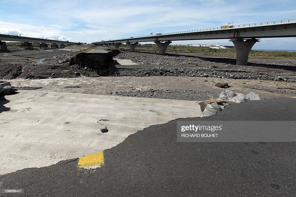 General view from a remaining piece of road crossing the river that links Saint Louis de la Reunion with Saint Pierre on January 4, 2013 near Saint Louis, on the French island of La Reunion, following the passing of cyclone Dumile. Winds of up to 180 kilometres per hour (110 miles per hour) and torrential rain caused extensive damage to the electricity network after cyclone Dumile passed within 90 kilometres of the island's west coast at around 0900 GMT. AFP PHOTO / RICHARD BOUHET