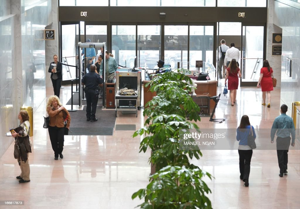 A general view from the inside of the Hart Senate Office Building shows people entering and leaving the building after it was re-opened on April 17, 2013 on Capitol Hill in Washington, DC. The building was closed earlier following reports of a suspicious package. AFP PHOTO/Mandel NGAN