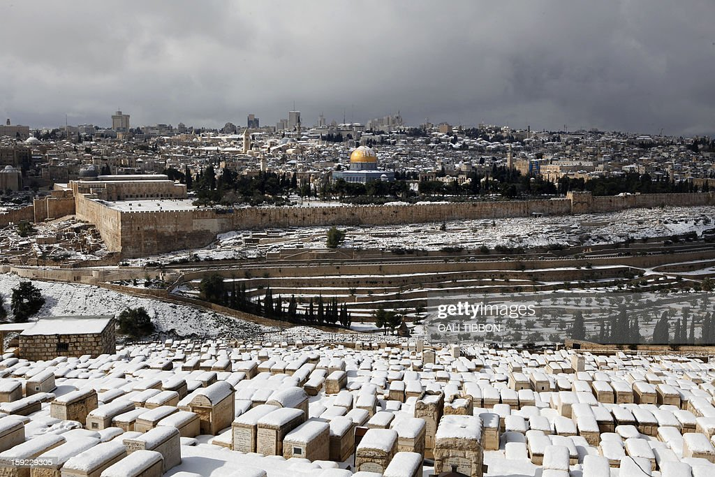 A general view from the Jewish cemetery at the Mount of Olives shows the snow-covered old city of Jerusalem on January 10, 2013. Jerusalem was transformed into a winter wonderland after heavy overnight snowfall turned the Holy City and much of the region white, bringing hordes of excited children onto the streets. AFP PHOTO/GALI TIBBON