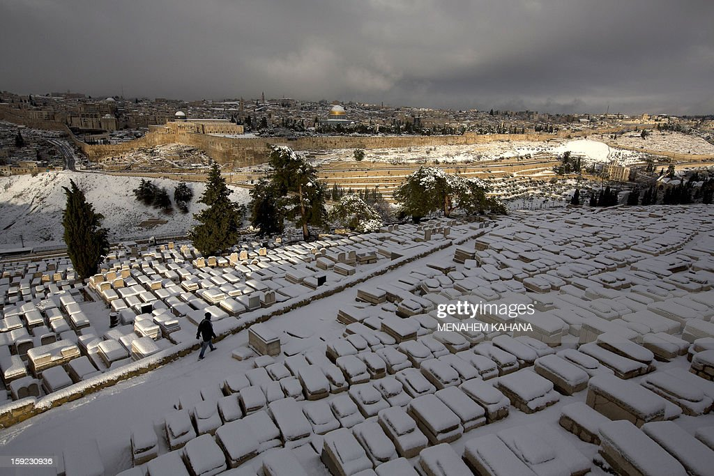 A general view from the Jewish cemetery at the Mount of Olives shows the snow-covered old city of Jerusalem on January 10, 2013. Jerusalem was transformed into a winter wonderland after heavy overnight snowfall turned the Holy City and much of the region white, bringing hordes of excited children onto the streets.