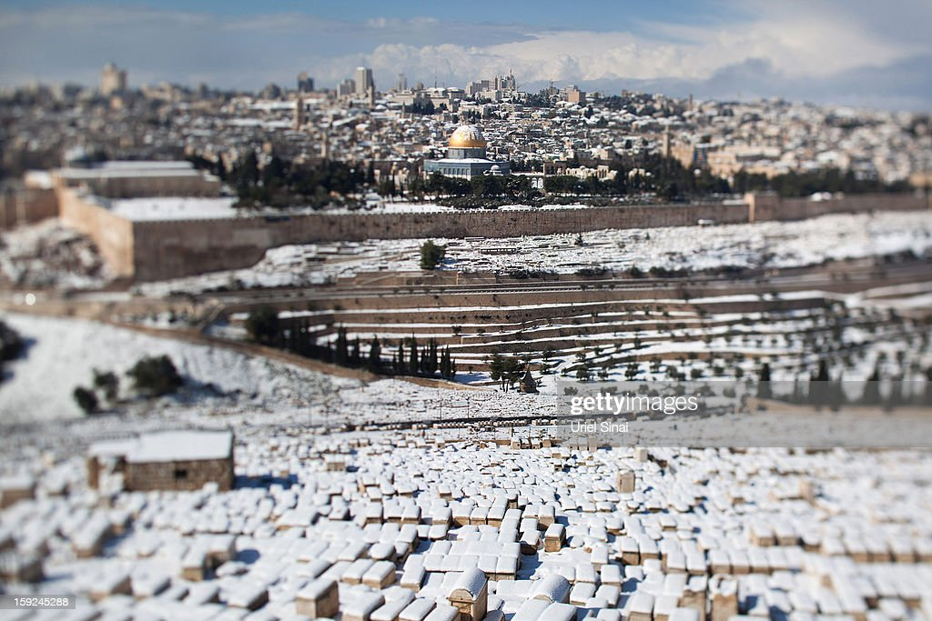 Image was created using a variable planed lens) A general view from the Jewish cemetery at the Mount of Olives shows the snow-covered old city of Jerusalem on January 10, 2013 in Jerusalem, Israel.