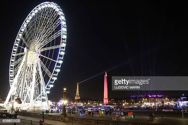 A general view from the Place de la Concorde shows the Ferris wheel the Eiffel Tower the obelisk and the Grand Palais illuminated in pink ahead of...