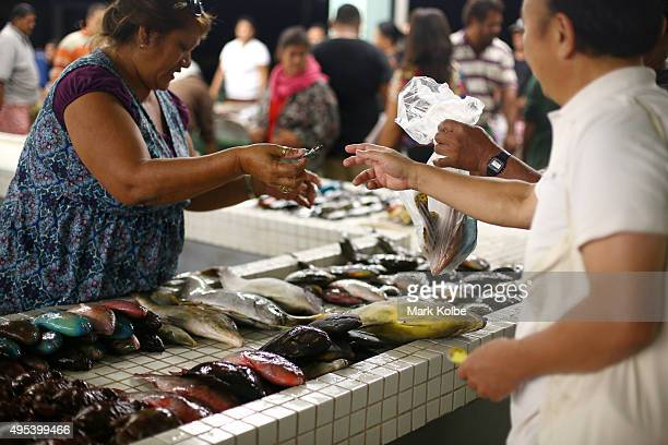 A general view is seen as a local buys fish from a vendor during Sunday morning trading at the Apia Fish Market on September 13 2015 in Apia Samoa...