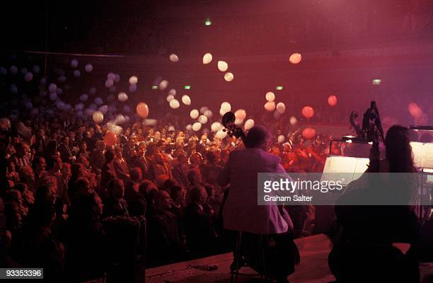 A general view of a classical orchestra performing on stage viewed from the side and showing the audience with balloons falling on to them circa 1998...
