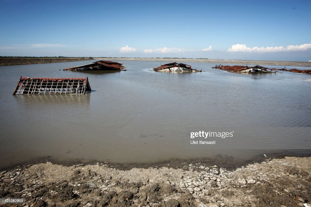 A general view of a destoryed factory building submerged in the mud from volcano 'Lusi' on May 30, 2010 in the subdistrict of Porong in Sidoarjo, East Java, Indonesia. Mud and gases continue to spew from Lusi four years after it first erupted, suspected to be triggered by the drilling activities of Indonesian oil and gas exploration company Lapindo Brantas. The initial eruption engulfed entire communities, wiping out villages and killing 13 people. Mud flow from the volcano continues at a rate of up to 150,000m3 per day, and to date has displaced tens of thousands of people.