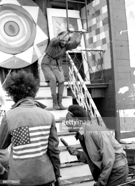 General view of a group of people with an American flag on a jacket a man holding onto an escape ladder and a woman holding a popsicle stick circa...