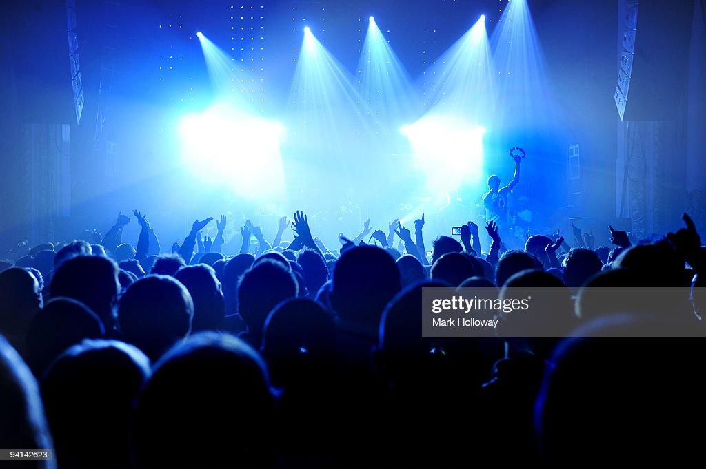 A general view of a rock gig from the back of the venue showing the backs of the heads of the audience and arms raised towards the brightly lit stage...