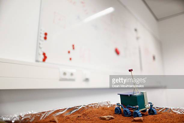 A general view of a whiteboard used for ideas in the lunch room as well as a mini Mars Rover model in a small orange sand tray with rocks...