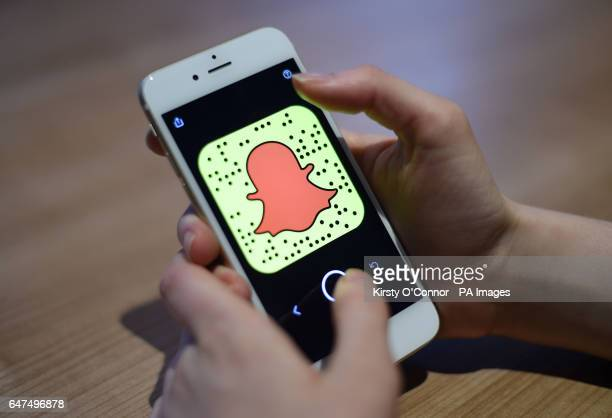 A general view of a woman holding a mobile phone with the Snapchat app