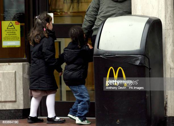 A general view of a woman leading two children into a McDonald's restaurant in Bristol city centre