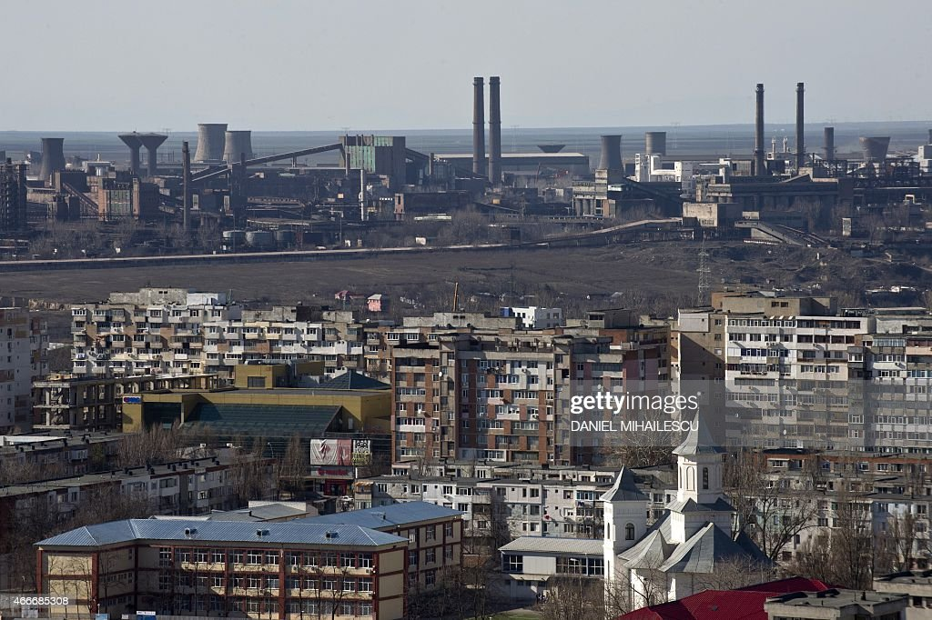 A general view of blocks of flats backdropped by Arcelor Mittal's steel mill on March 4 2015 in Galati The city was home to a community of some 13000...