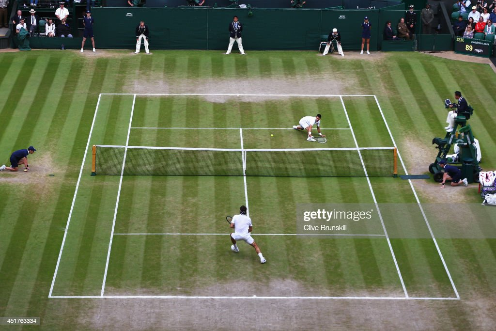 General view of centre court as Novak Djokovic of Serbia plays a volley at the net during the Gentlemen's Singles Final match against Roger Federer...