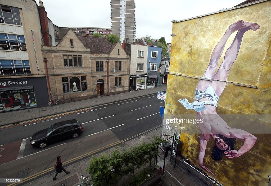 General view of Cosmo Sarson's mural of Jesus breakdancing that he has painted on the 8.5 metre wall beside The Canteen in Stokes Croft and is being officially unveiled this evening is reflected in a window, on June 11, 2012 in Bristol, England. The artist was commissioned by The Canteen to paint the wall, which is directly opposite Banksy's Mild Mild West. The controversial 'Breakdancing Jesus', which took 4 days to paint and involved a kilo of glitter and was inspired by an actual event in the Vatican where breakdancers performed to an applauding Pope John Paul II in 2004, is likely to be the latest attraction for graffiti tourists visiting Bristol, often seen the spiritual home of underground artist Banksy.