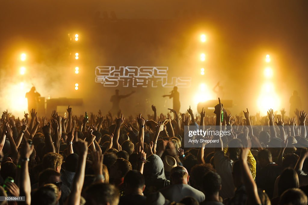 A general view of crowds cheering and watching the stage in the audience at a concert as Chase Status perform on stage during the final day of...