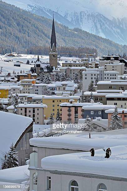 A general view of Davos and its St John's Church is seen as Swiss army soldiers dig snow trenches on a roof on January 10 2012 in Davos Switzerland...