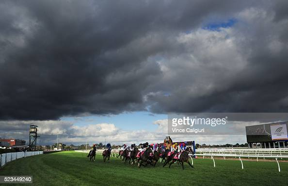 General view of Dwayne Dunn riding Nudierudie winning race 7 as the dark clouds hover over course during Melbourne Racing at Caulfield Racecourse on...