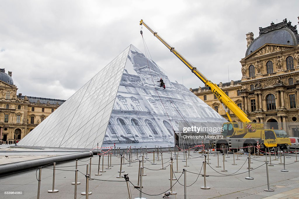 A general view of French street artist JR's artwork outside The Louvre on May 24, 2016 in Paris, France. The artist has covered The Louvre Pyramid by an optical illusion made with black and white photos of 16th century buildings and is open to the public from May 25 to June 27, 2016.