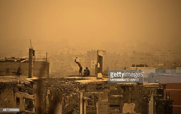 A general view of Gaza City shows Palestinian workers removing debris from buildings which were destroyed during the 50day war between Israel and...