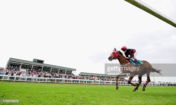 A general view of horses and jockeys passing the grand stand during racing at Yarmouth racecourse on June 12 2013 in Yarmouth England