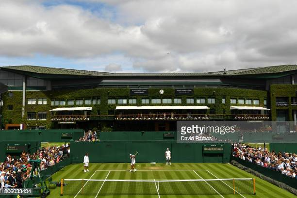 A general view of Rafael Nadal of Spain plays a backhand as coach Toni Nadal looks on during a practice session on day one of the Wimbledon Lawn...