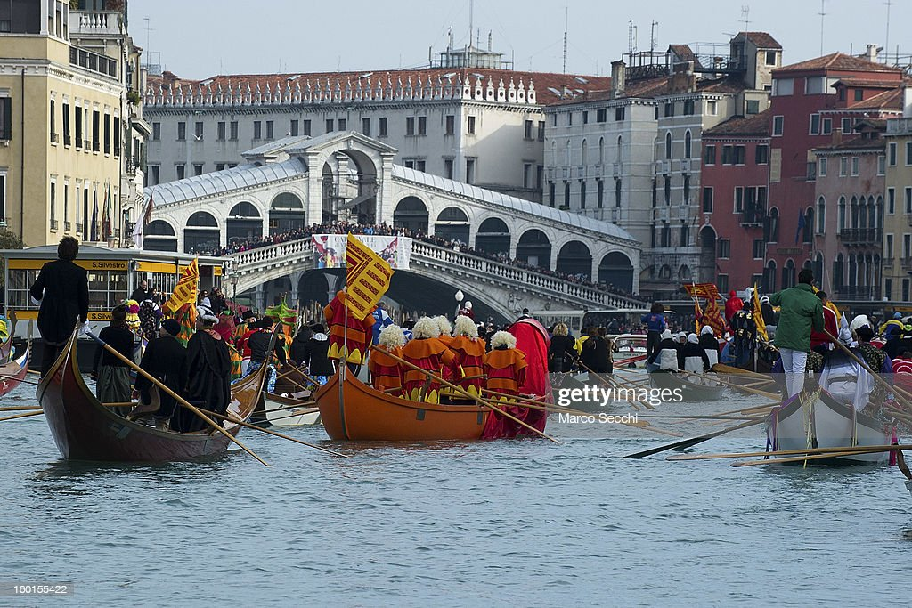 A general view of rowers dressed with costumes and masks taking part in the Water Parade while they pass under the Rialto Bridge on the Grand Canal on January 27, 2013 in Venice, Italy. The 2013 Carnival of Venice will run from January 26 - February 12 and includes a program of gala dinners, parades, dances, masked balls and music events.