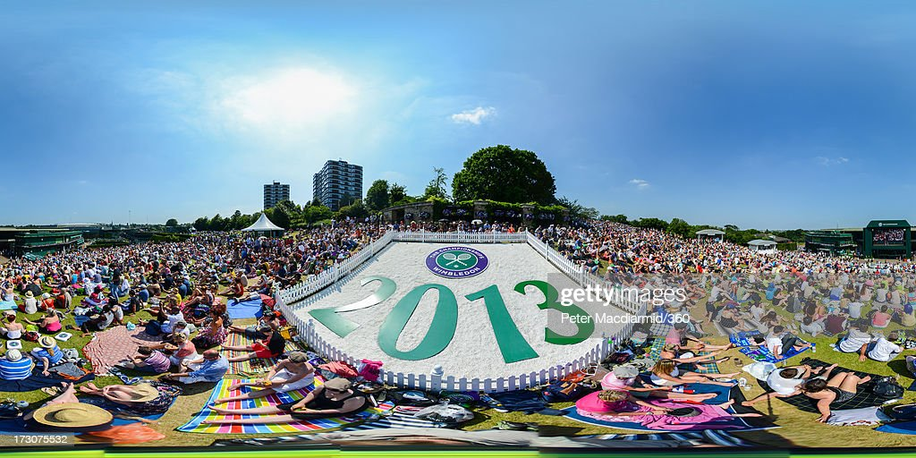 General view of spectators watching a giant TV screen from Murray Mound showing during the Ladies' Singles final match between Sabine Lisicki of Germany and Marion Bartoli of France on day twelve of the Wimbledon Lawn Tennis Championships at the All England Lawn Tennis and Croquet Club on July 6, 2013 in London, England.