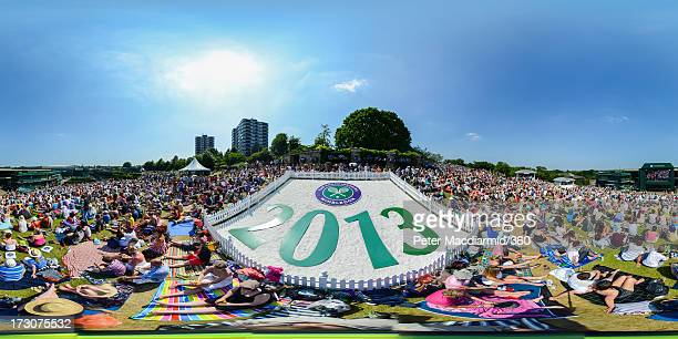 General view of spectators watching a giant TV screen from Murray Mound showing during the Ladies' Singles final match between Sabine Lisicki of...
