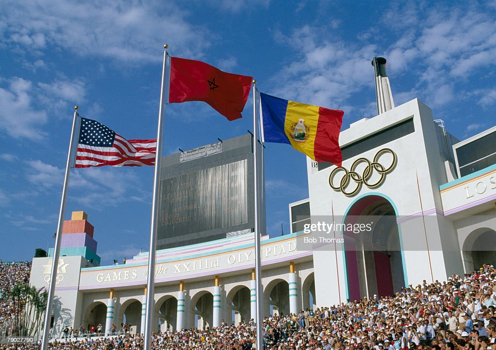 General view of spectators watching a medal ceremony with national flags flying inside the Los Angeles Memorial Coliseum during the 1984 Summer...