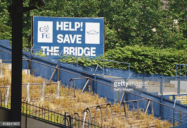 A general view of Stamford Bridge home of Chelsea FC shows a 'Help save the Bridge' sign and it's overgrown terraces circa 1989 in London England