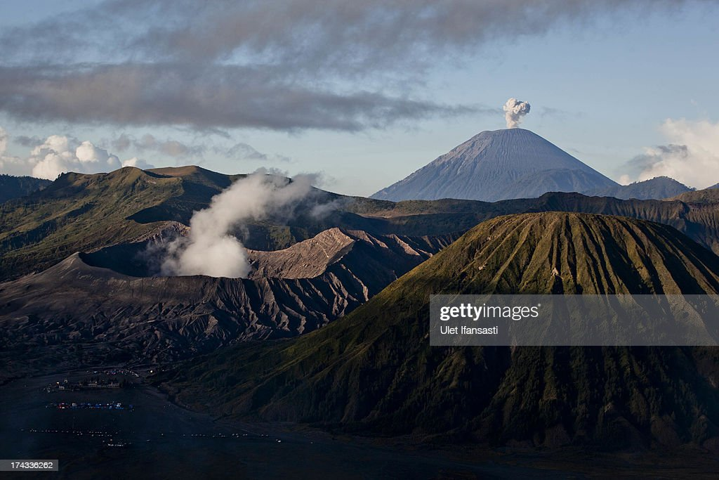 General view of the Bromo Tengger Semeru National Park, showing Mount Bromo, Mount Semeru and Mount Batok, the location of the Tenggerese villages where the Tenggerese Hindu Yadnya Kasada Festival is held, in the background, on July 23, 2013 in Probolinggo, Indonesia. The festival is the main festival of the Tenggerese people and lasts about a month. On the fourteenth day, the Tenggerese make the journey to Mount Bromo to make offerings of rice, fruits, vegetables, flowers and livestock to the mountain gods by throwing them into the volcano's caldera. The origin of the festival lies in the 15th century when a princess named Roro Anteng started the principality of Tengger with her husband Joko Seger, and the childless couple asked the mountain Gods for help in bearing children. The legend says the Gods granted them 24 children but on the provision that the 25th must be tossed into the volcano in sacrifice. The 25th child, Kesuma, was finally sacrificed in this way after initial refusal, and the tradition of throwing sacrifices into the caldera to appease the mountain Gods continues today.
