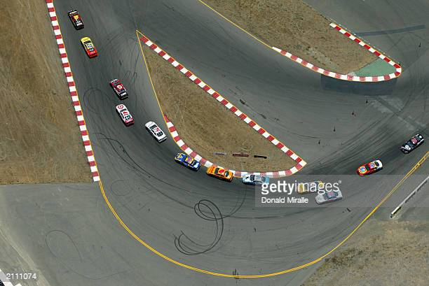 A general view of the cars taking a turn in a pack during the NASCAR Winston Cup Dodge Save Mart 350 at the Infineon Raceway on June 22 2003 in...