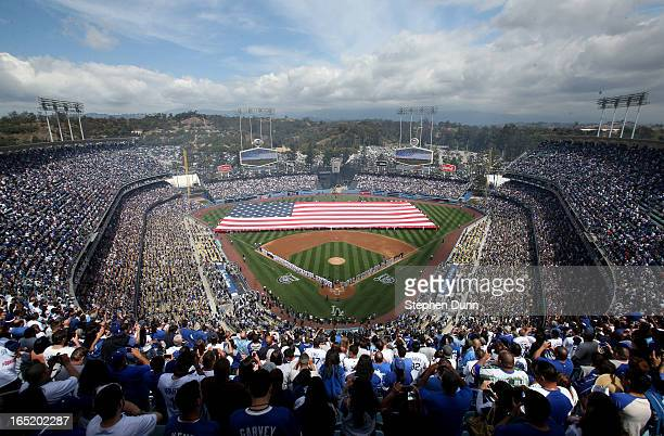 General view of the crowd and participants stand for the national anthem as a giant Americdan flag is unfurled on the field before the game between...