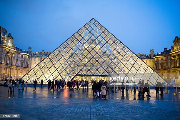A general view of the Louvre museum with the entrance pyramide is pictured in the evening on February 28 2014 in Paris France The museum is housed in...