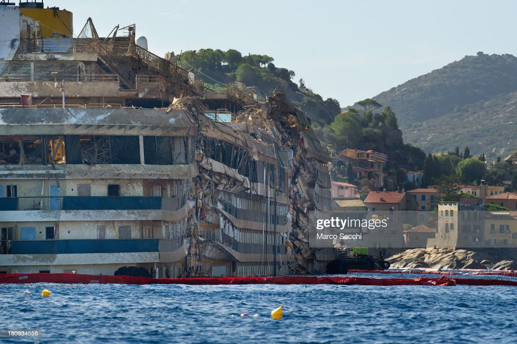 General view of the previously submerged, severely damaged right side of the Costa Concordia cruise ship in upright position on September 18, 2013 in Isola del Giglio, Italy. The vessel, which sank on January 12, 2012, was successfully righted during a painstaking operation yesterday morning. The ship will eventually be towed away and scrapped. It was the first time the procedure, known as parbuckling, had been carried out on a vessel as large as Costa Concordia.