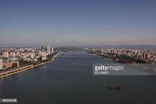 A general view of the Pyongyang city skyline shows the landmark Juche tower and the Kim IlSung stadium along the Taedong river on October 12 2015...