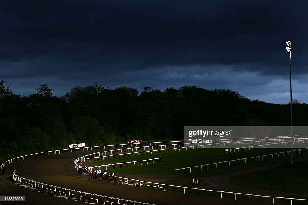 A general view of the race course and the runners and riders during the Mix Business With Pleasure Handicap Stakes race during evening flat races at Kempton Park on May 8, 2013 in Sunbury, England.