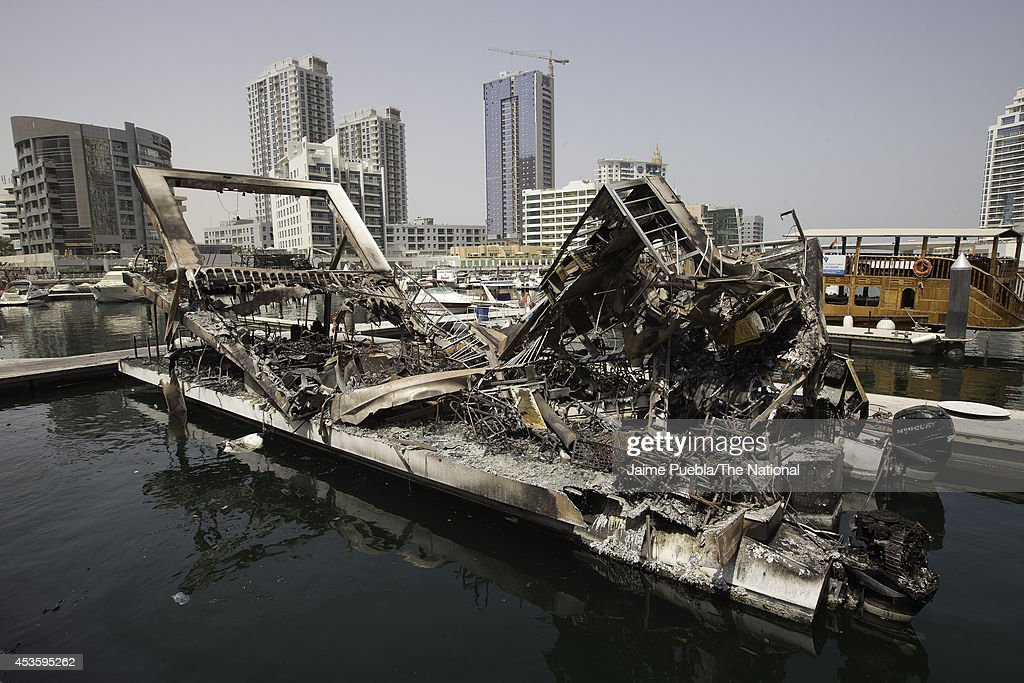 A general view of the remains of the burnt restaurant boat, moored near Al Rahim Mosque in Dubai Marina on August 14, 2014 in Dubai, United Arab Emirates. Passengers were forced to jump out of the boat's windows to escape the flames.