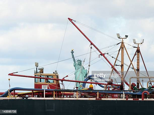 A general view of the Statue of Liberty in the New York Harbor with a ship passing in front of it as photographed on April 27 2012 from the Red Hook...