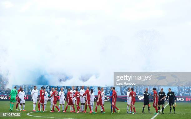General view of the two teams shaking hands for fairplay and the smoke from the pyrotechnics from the fans behind them prior to the Danish cup DBU...
