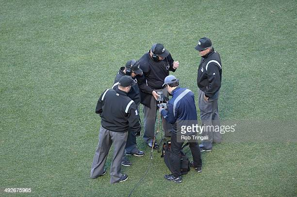 A general view of the Umpires huddled up taking a look at Instant Replay during the game between the New York Mets and the Washington Nationals on...