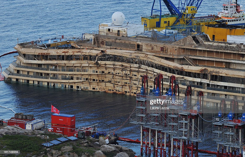 A general view of the uprighted Costa Concordia is seen on September 22, 2013 in Giglio Porto, Italy. The search will be resumed for the missing bodies of Maria Grazia Tricarichi and Russsel Rebello, whose bodies were never found after the Costa Concordia capsized on January 13, 2012, leaving 32 people dead. Specialist divers from the coastguard, fire brigade and police will search the area between the righted ship and the coast and other parts of the vessel which were previously off limits.