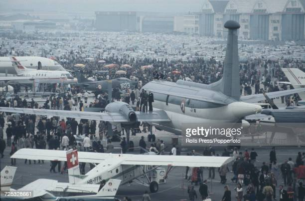 General view of various aircraft pictured on display with crowds of spectators surrounding them at Le Bourget Airport during the 1971 Paris Air Show...