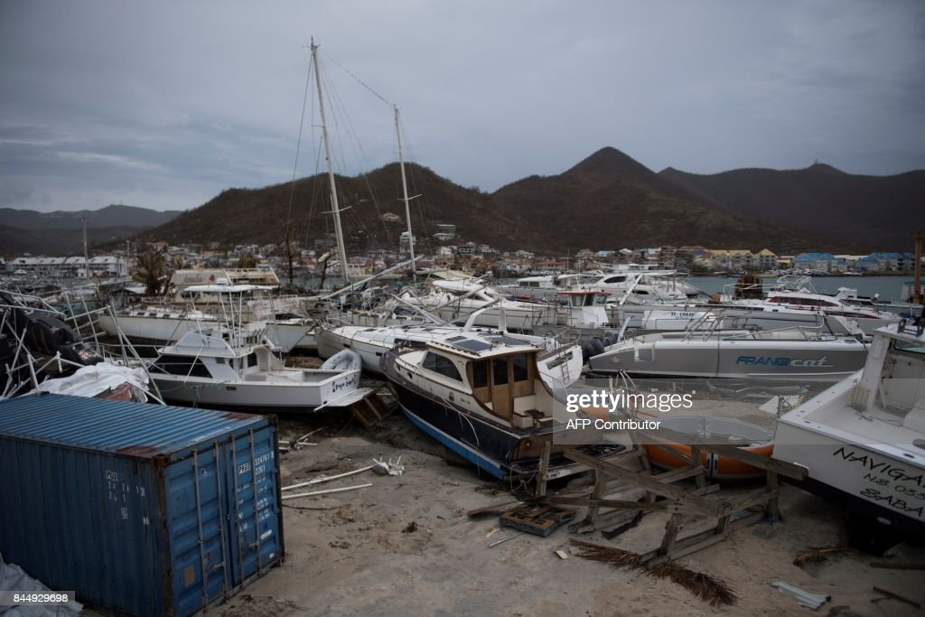 TOPSHOT - General view of wrecked boats in Geminga shipyard in Marigot, taken on September 9, 2017 in Saint-Martin island devastated by Irma hurricane. Officials on the island of Guadeloupe, where French aid efforts are being coordinated, suspended boat crossings to the hardest-hit territories of St. Martin and St. Barts where 11 people have died. Two days after Hurricane Irma swept over the eastern Caribbean, killing at least 17 people and devastating thousands of homes, some islands braced for a second battering from Hurricane Jose this weekend. / AFP PHOTO / Martin BUREAU