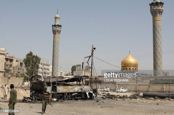 A general view shows a bombed bus outside a Shiite holy shrine in the Sayyida Zeinab suburb of Damascus after a suicide car bomb exploded there early...