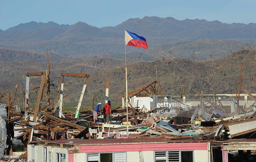 A general view shows a Philippines flag flying above the destruction caused by Typhoon Bopha in the town of Cateel, Davao Oriental on December 11, 2012. The United Nations launched a 65 million USD global appeal on December 10 to help desperate survivors of a typhoon that killed more than 600 people and affected millions in the southern Philippines.