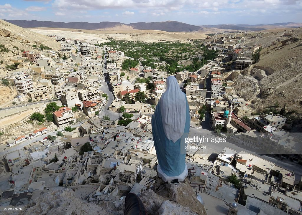 A general view shows a statue of the Virgin Mary overlooking the ancient Christian town of Maalula, 56 kilometers northeast of the Syrian capital Damascus, on May 6, 2016, two years after the battle for Maalula ended. The battle for Maalula lasted seven months, with the Syrian army finally expelling opposition forces, including Al-Qaeda affiliate Al-Nusra Front, in mid-April 2014. / AFP / STRINGER