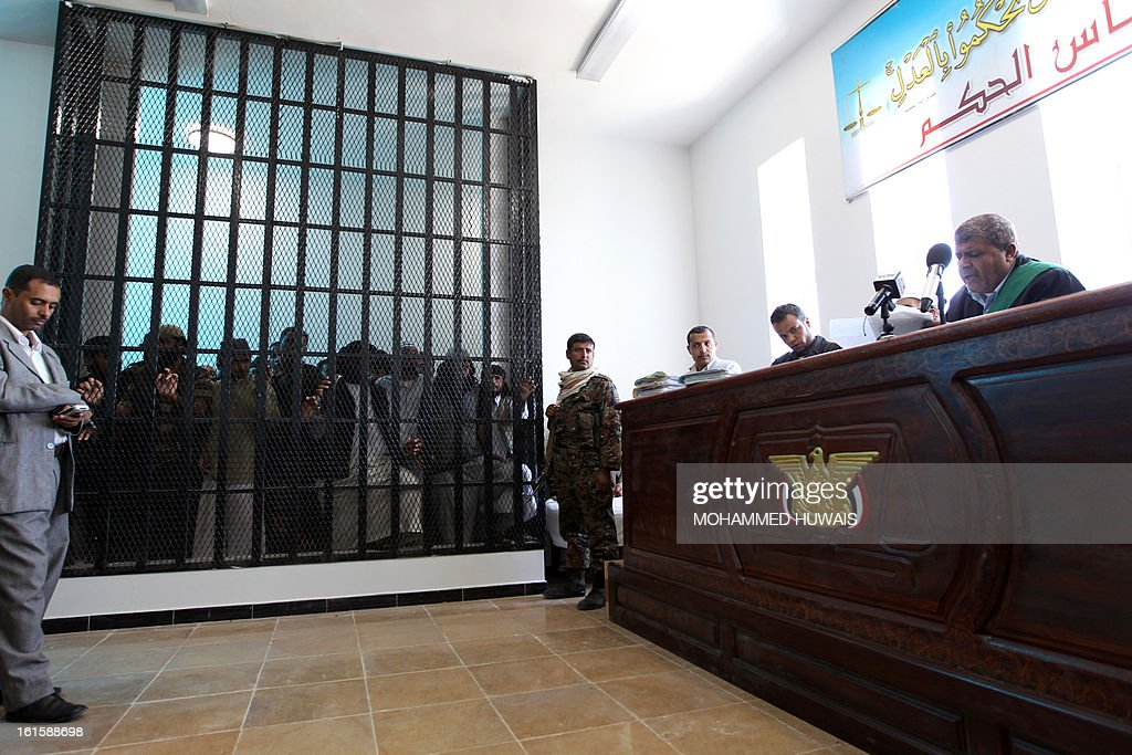 A general view shows a Yemeni judge (R) handing down various sentences on suspected al-Qaeda militants being held in a barred caged, at the state security appeals court in the capital Sanaa, on February 12, 2013. Twenty four suspects were indited to various prison terms.