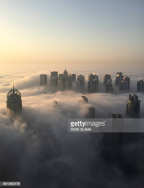 A general view shows an early morning fog covering the skyline of part of the city of Dubai on October 5 2015 AFP PHOTO / RENE SLAMA