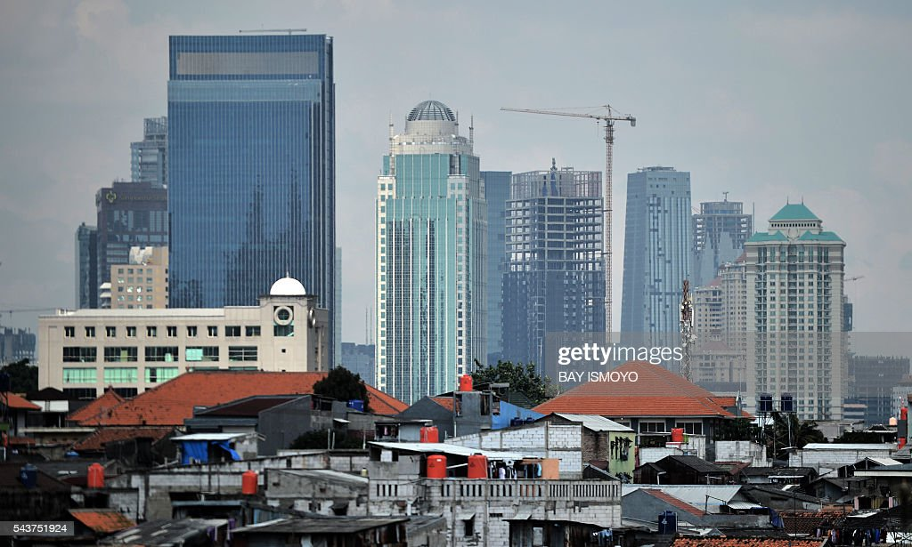 A general view shows an under-construction building (C) among the city skyline in Jakarta on June 30, 2016. Indonesia launched a tax amnesty in a bid to give Southeast Asias top economy a multibillion-dollar boost, defying criticism the move will let evaders off the hook. / AFP / BAY