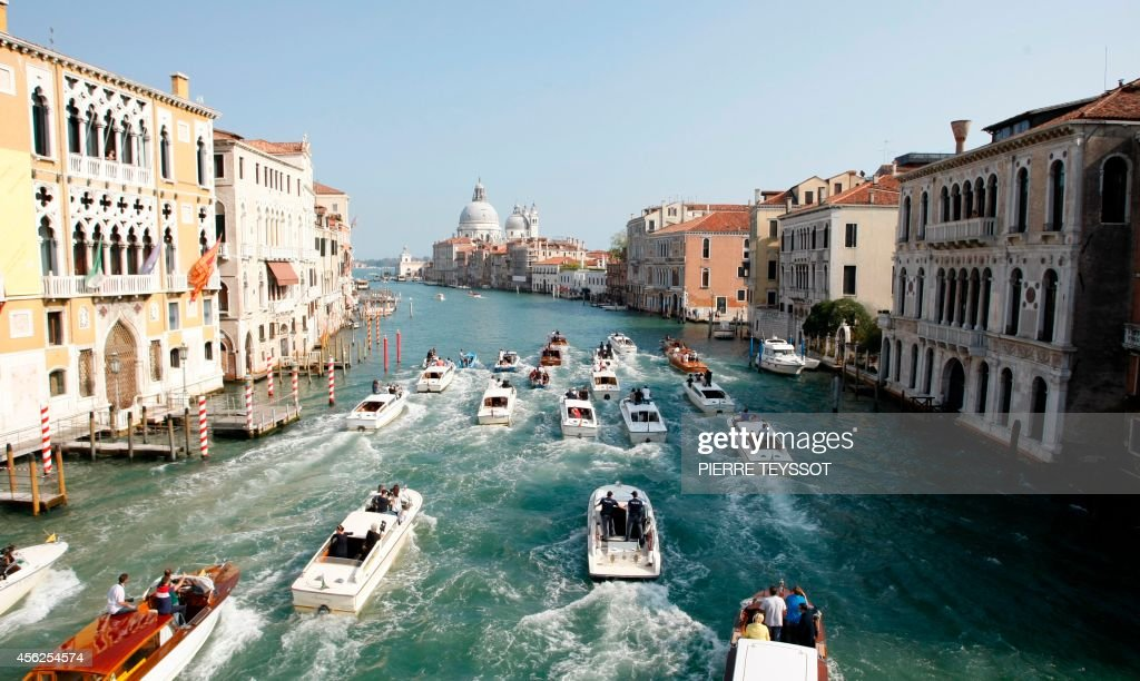 A general view shows boats surrounding the taxi boat of US actor George Clooney and his wife Amal Alamuddin on September 28 2014 on the Grand Canal...